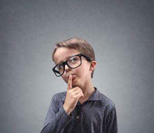 A boy wearing glasses thinking